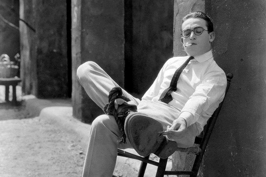 Harold Lloyd leaning back in chair smoking cigarette