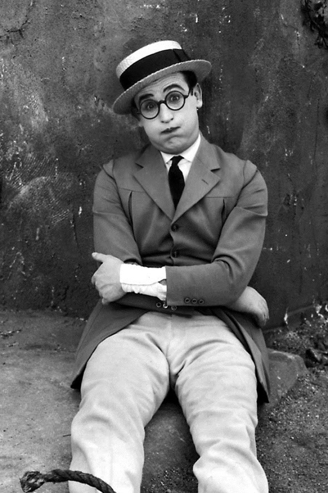 Harold Lloyd sitting on ground making funny face wearing hat suit and glasses