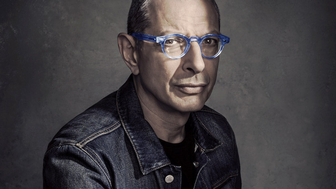 Jeff Goldblum wearing round blue glasses frames and denim jacket