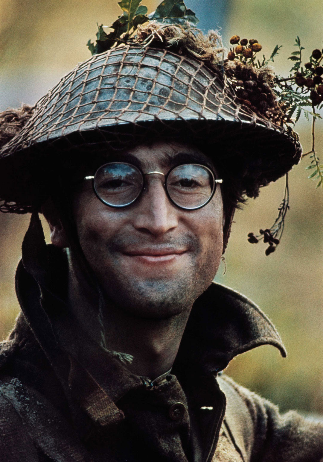 John Lennon wearing army helmet and round wire glasses smiling