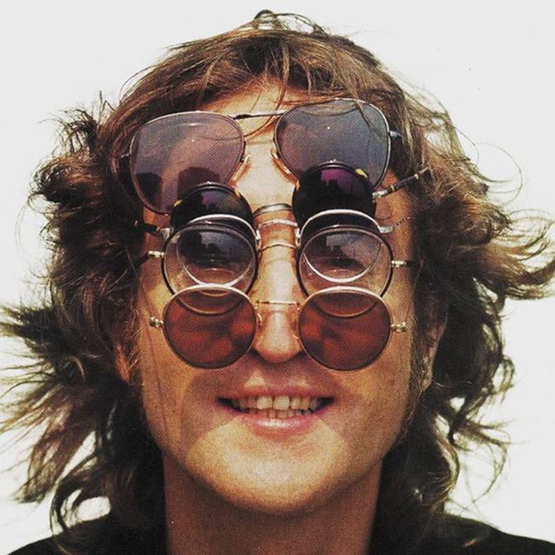 John Lennon wearing numerous round rim spectacles and sunglasses all on his head and face at once