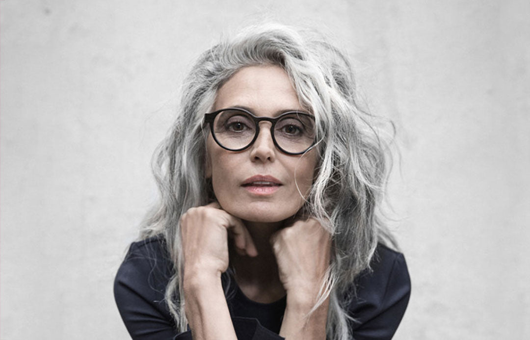 Lady with long grey hair wearing round black glasses