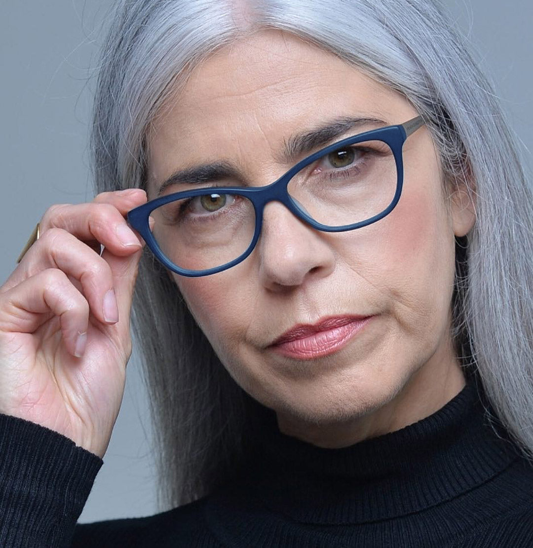 Lady with long straight grey hair touching her blue rimmed glasses frame