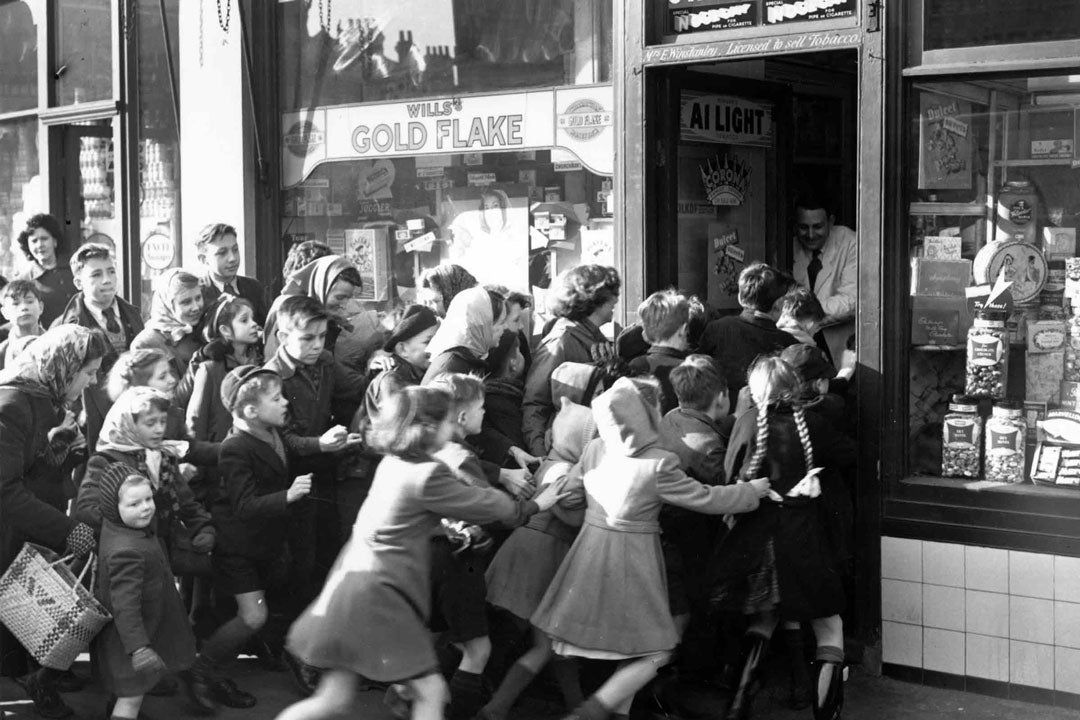 Large group of children rushing into shop in 1951