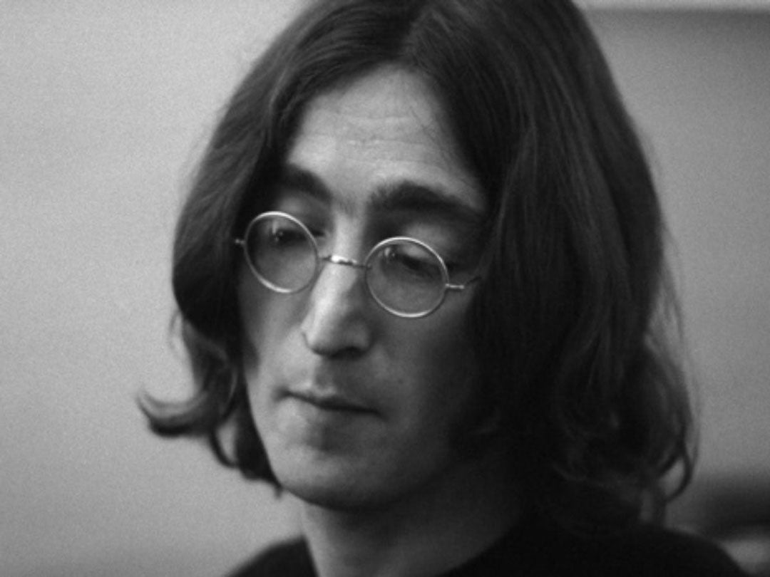 Long haired John Lennon wearing his iconic round wire glasses loowking downwards