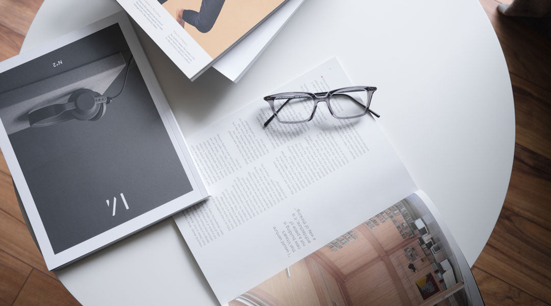 Magazines and grey glasses on top of white circular coffee table