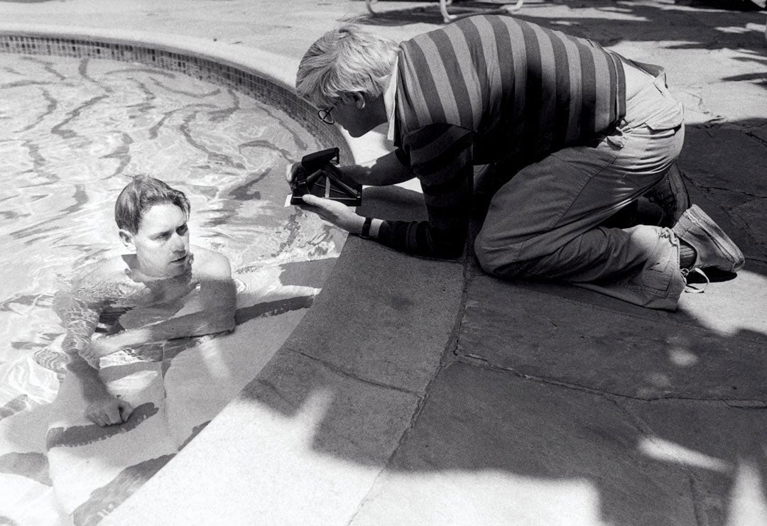 Man in a swimming pool with David Hockney kneeling at the edge taking his photograph