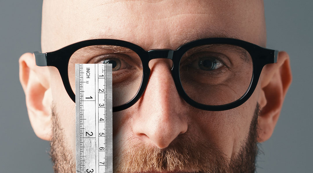 Man measuring his ocular height with a white ruler