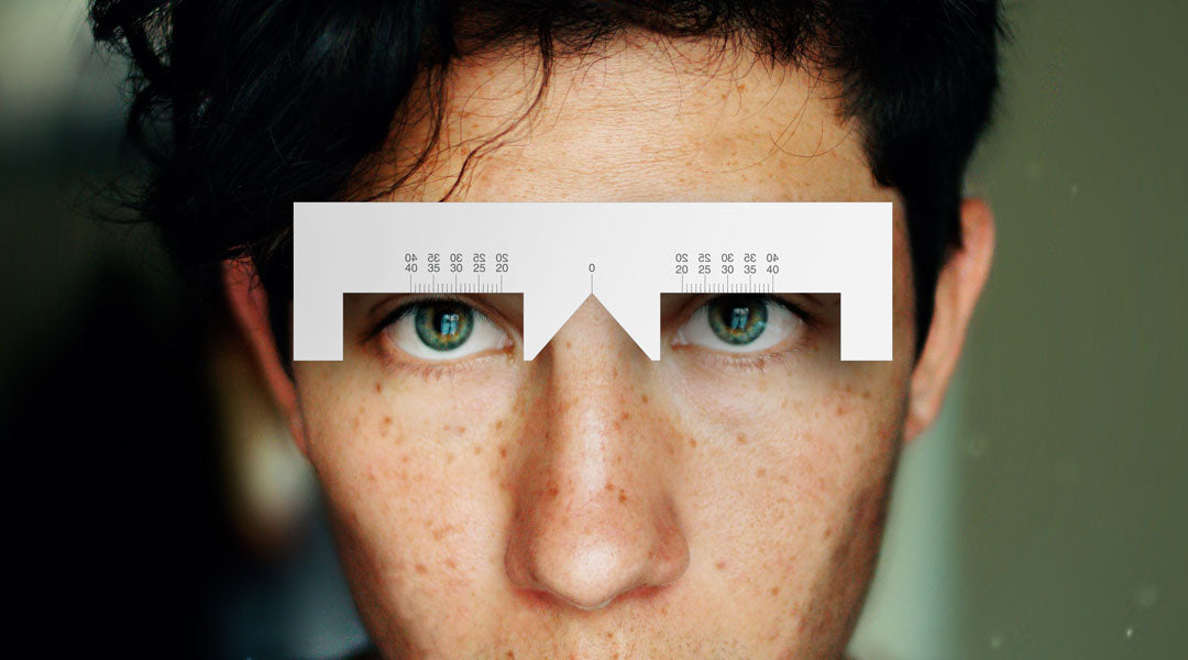 Man measuring his pupillary distance using an optical PD ruler