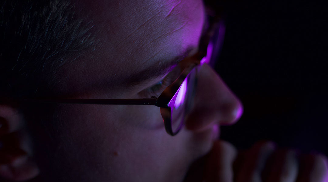 Man sitting at computer wearing blue light glasses