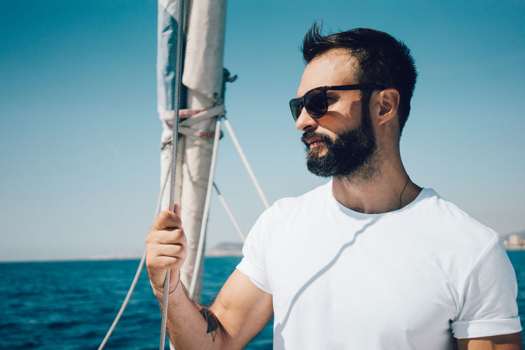 Man wearing white Tshirt and sunglasses standing on a yacht looking out to sea