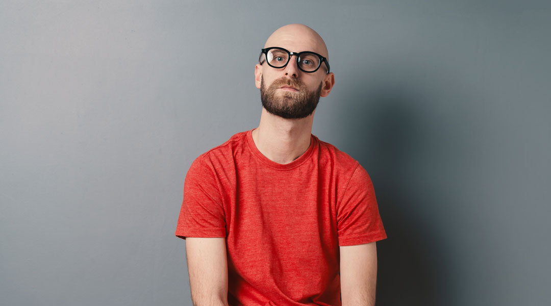 Man with no hair wearing thick black glasses and red T shirt