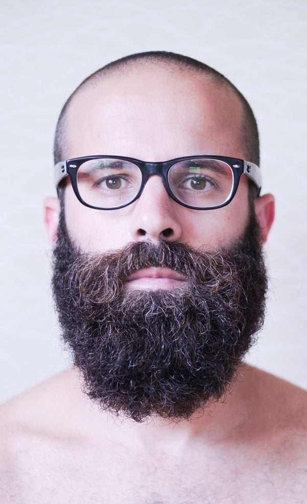 Man with shaved head and glasses wearing no shirt