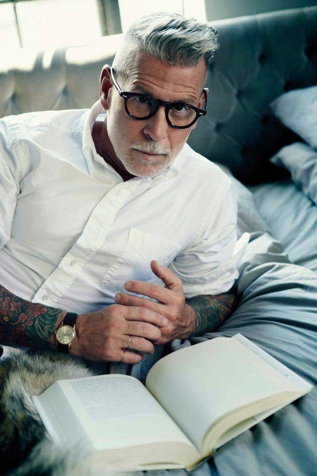 Man with short grey hair and tatoos lying on his side reading a book wearing thick dark spectacle frame