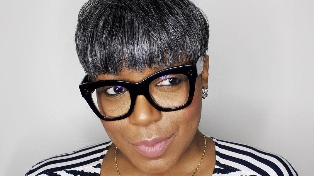 Mature African woman wearing a chunky rectangular pair of glasses with striped top looking away from camera
