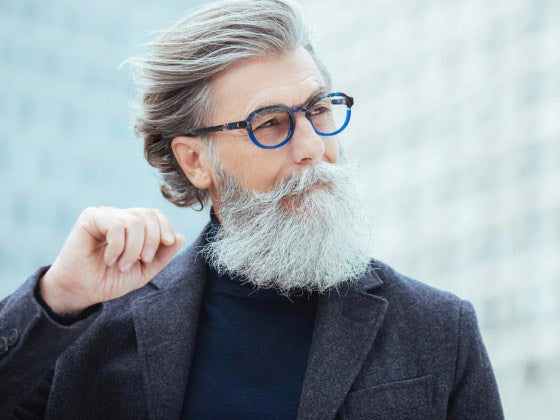 Mature man with swept back grey hair and long beard wearing quirky blue spectacle frame