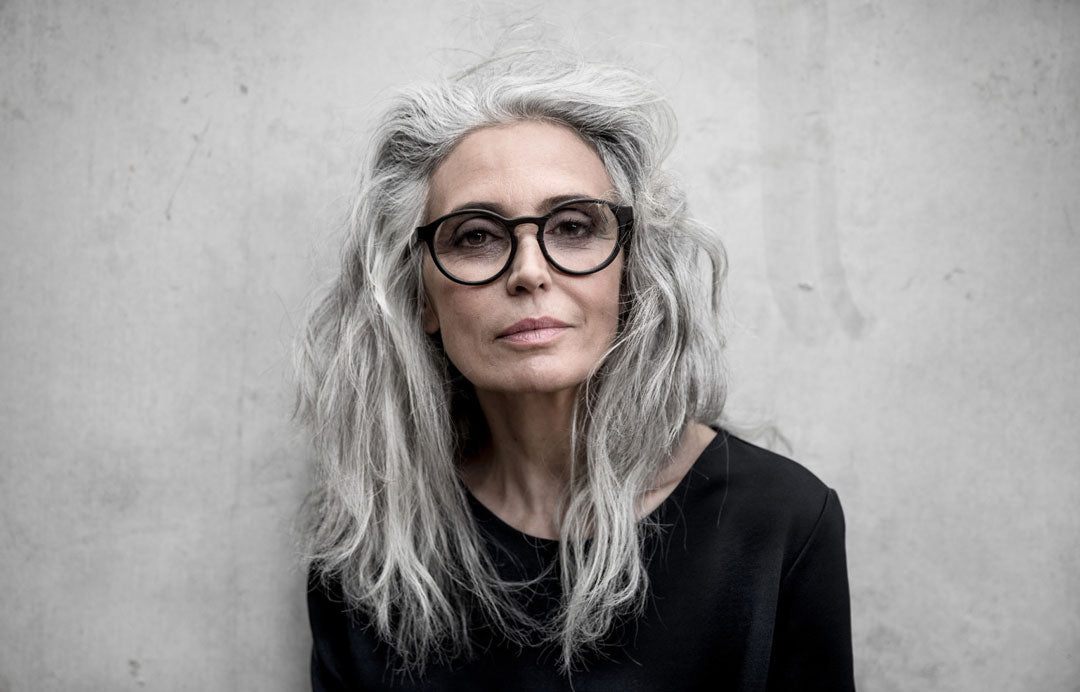 Mature woman with grey hair wearing round black glasses