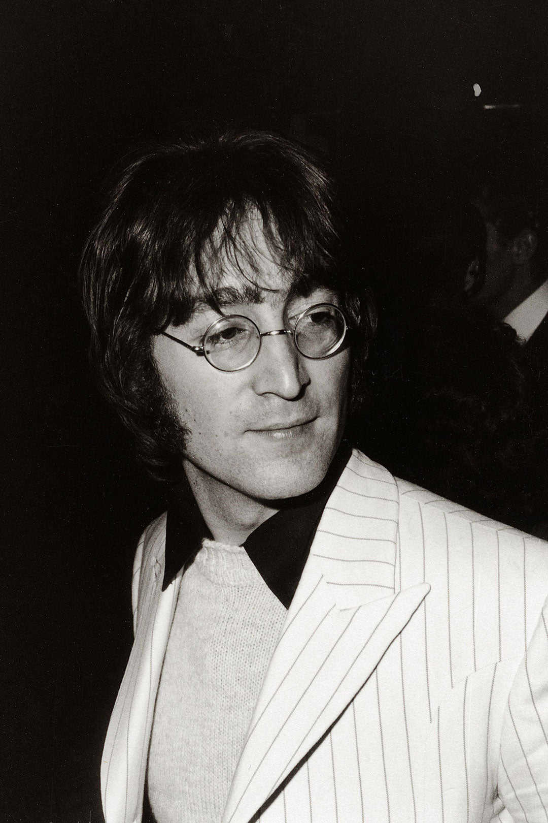 Music star John Lennon wearing pin striped white suit and round wire glasses frame