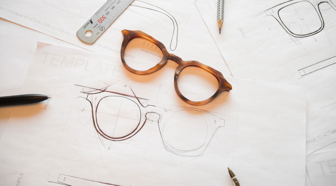 Octagonal orange sunglasses frame surrounded by drawing utensils lying upon white paper templates