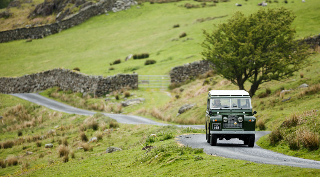 Old green Land Rover driving up country road
