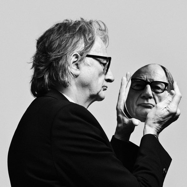 Paul Smith holding a mirror looking into it.