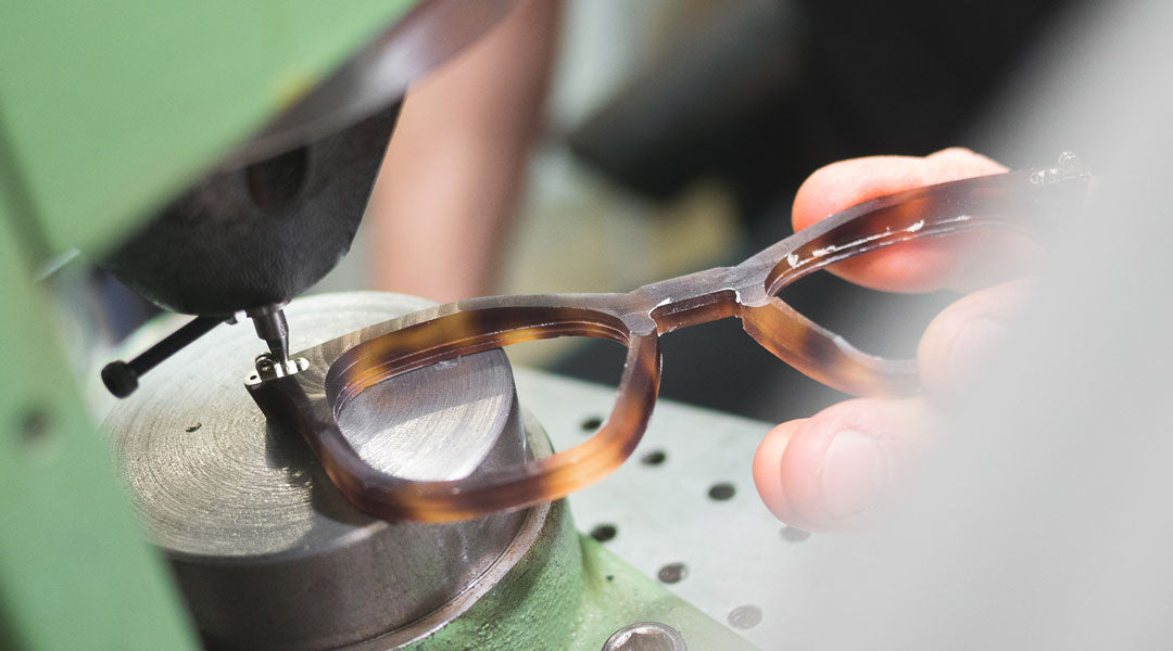 Orange and black sunglasses frame being fitted with hinges using a green machine