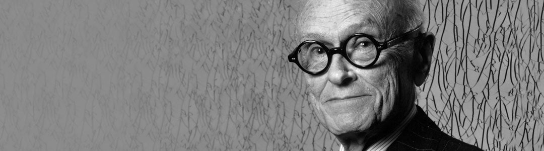 Philip Johnson wearing a suit and his black architect glasses