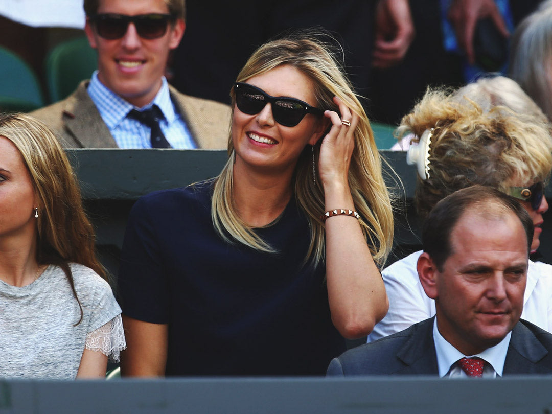 Professional tennis player Maria Sharapova in the crowd at Wimbledon smiling wearing square black sunglasses