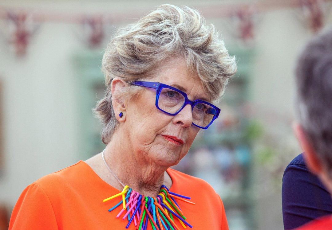 Prue Leith looking stern in her bright blue spectacle frame and orange blouse in the Great British Bake off tent