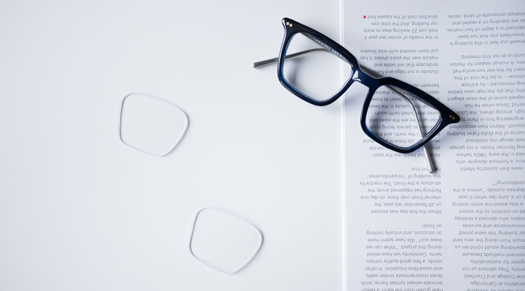 Rectangular blue reading glasses upon white table and magazine