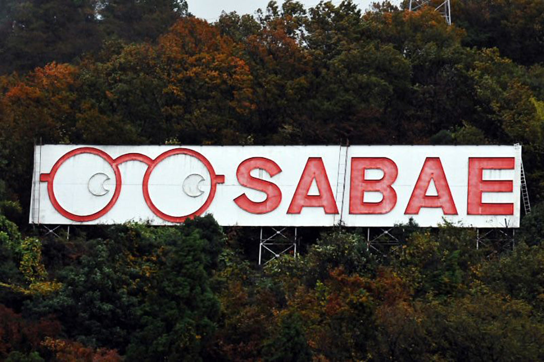 Red and white Sabae city signpost with glasses icon