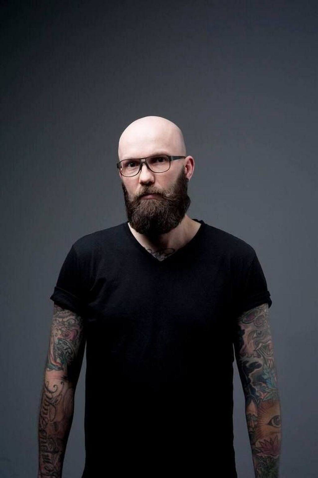 Serious-looking Caucasian bald man with tattoos beard and glasses