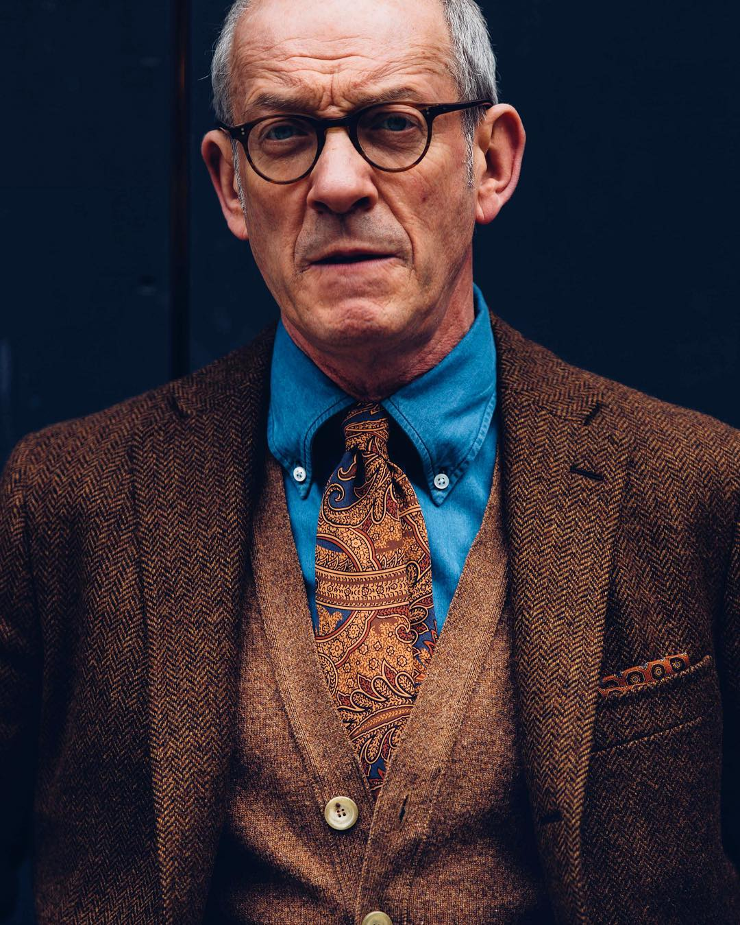 Serious looking man with blue shirt and brown suit jacket wearing round tortoise spectacle frames