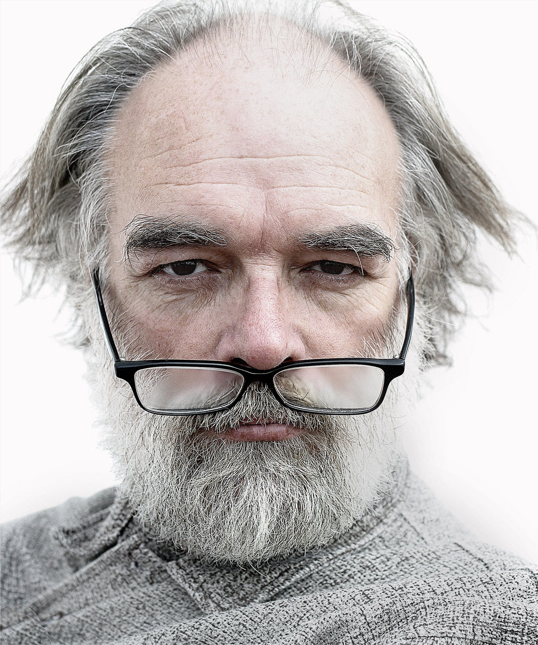 Serious looking man with long grey hair with his glasses humorously hanging off the end of his nose