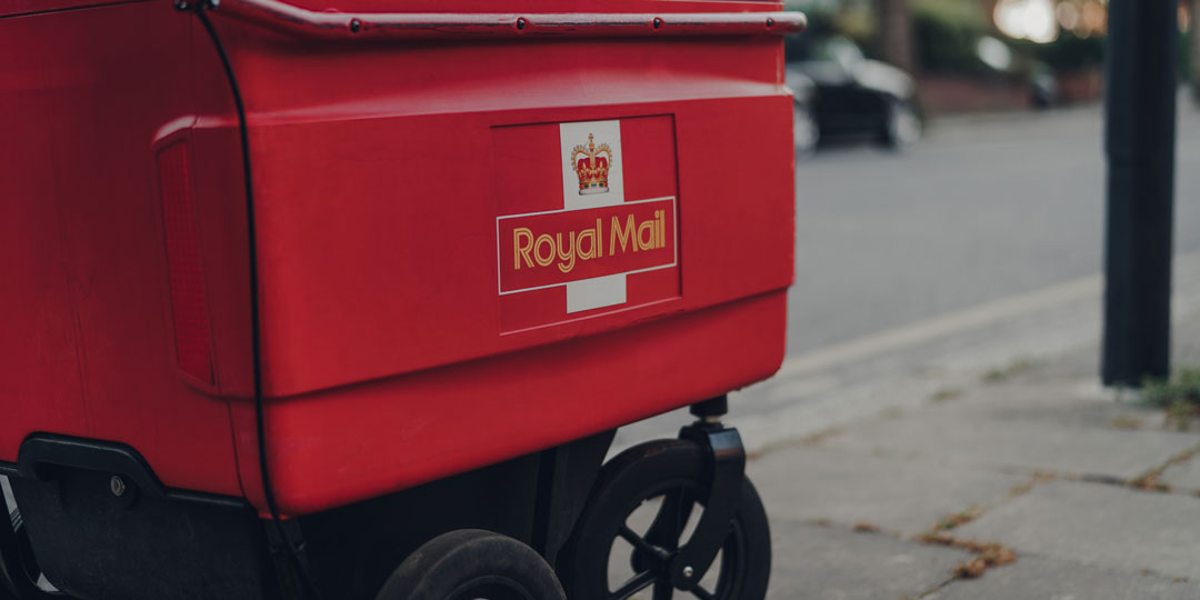 Side close view of Red Royal Mail parcel trolley in street