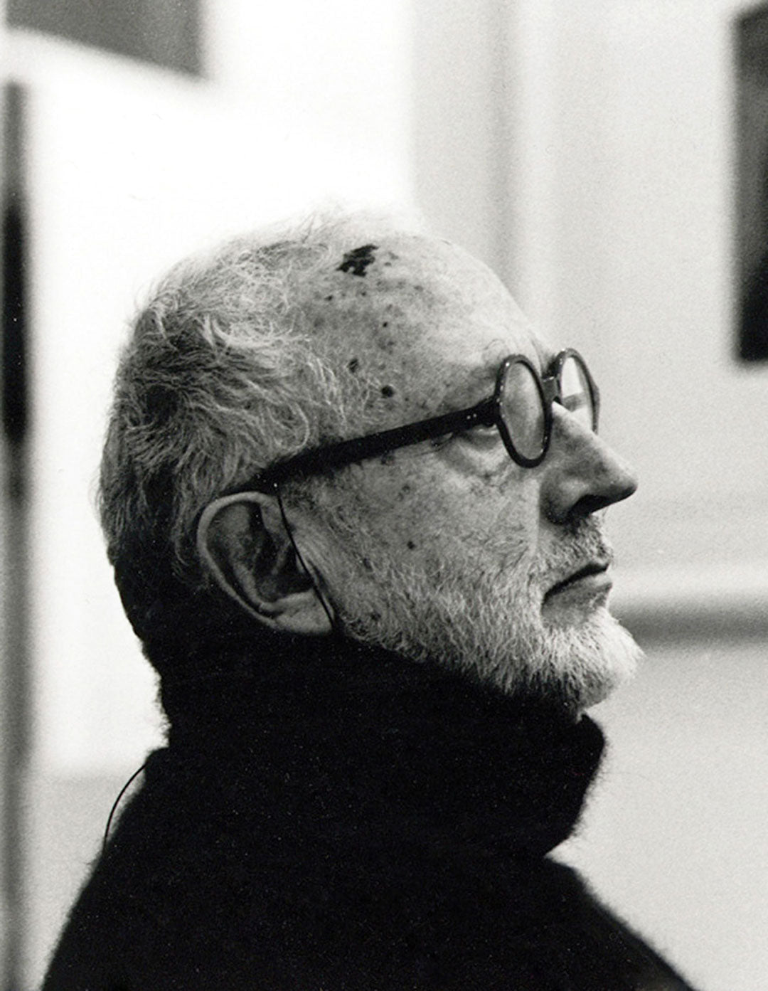 Side view of Architect Andrea Branzi wearing rollneck jumper and black round glasses frame