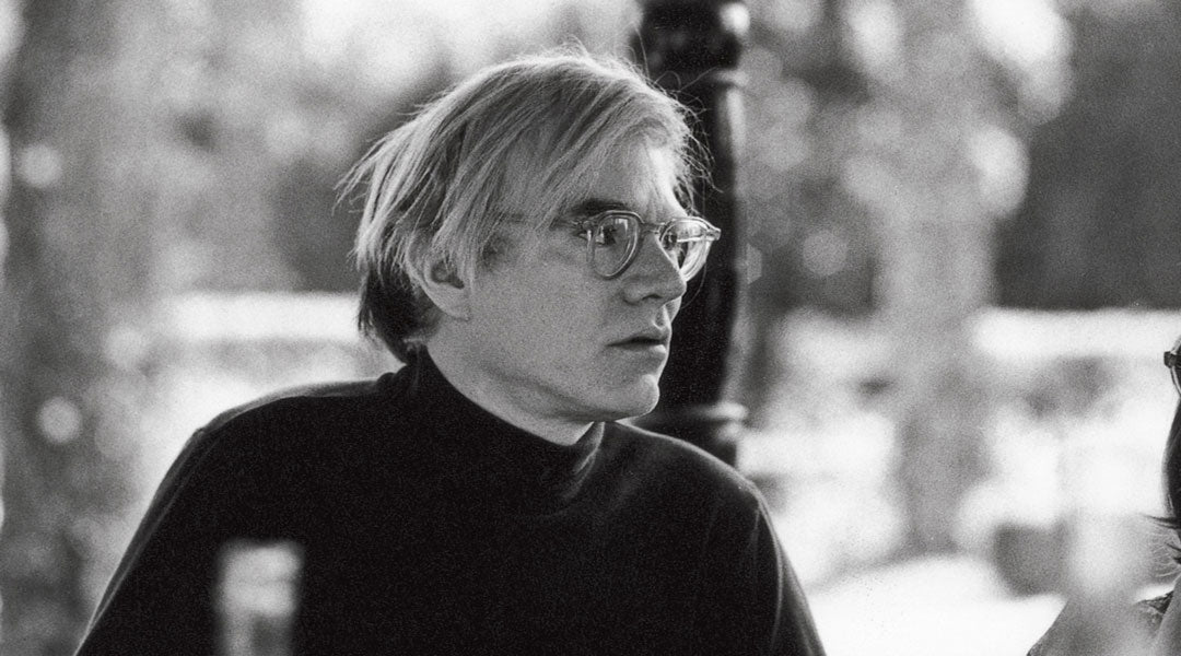 Side view of artist Andy Warhol wearing black polo neck and round clear glasses frame