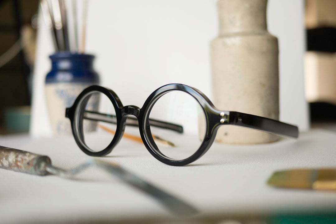 Side view of thick round black spectacles with straight arms