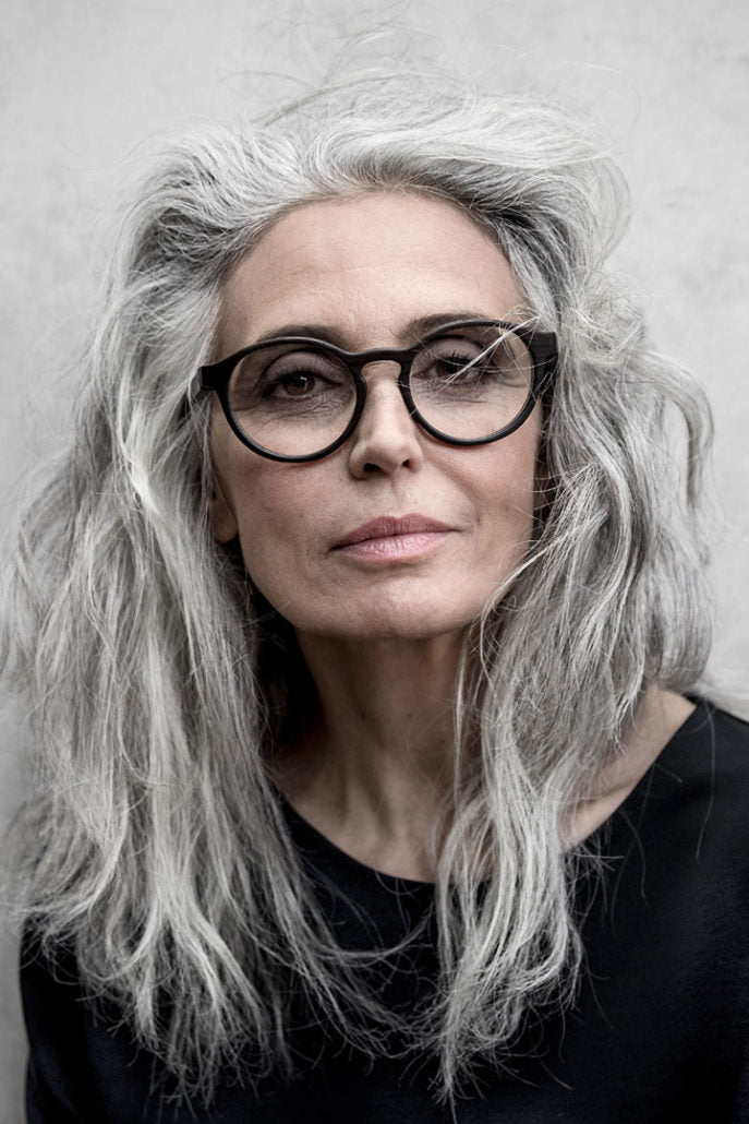 Silver haired female model wearing round dark glasses frame sitting face on