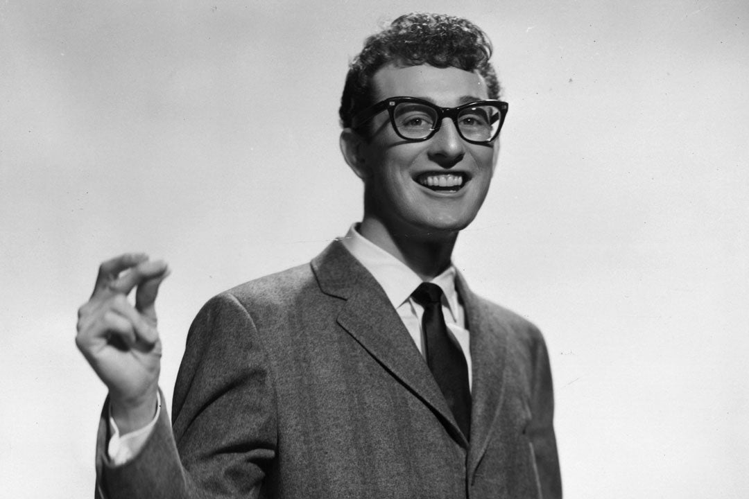 Singer Buddy Holly smiling wearing his thick rimmed glasses