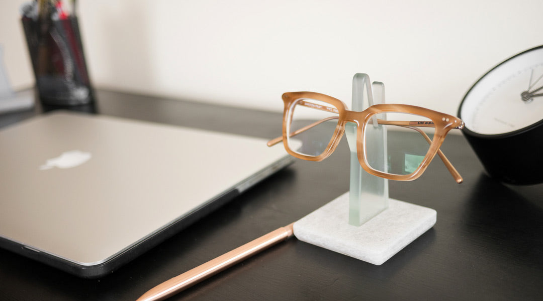 Spectacles resting on a glasses stand on black work desk
