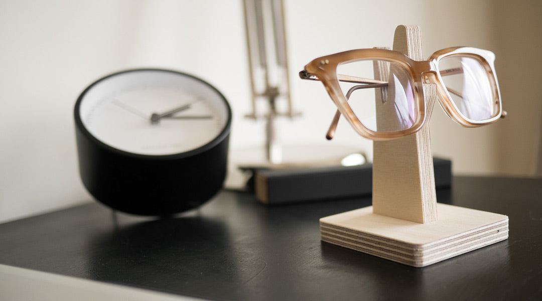 Spectacles resting on wooden eyeglass stand on office desk