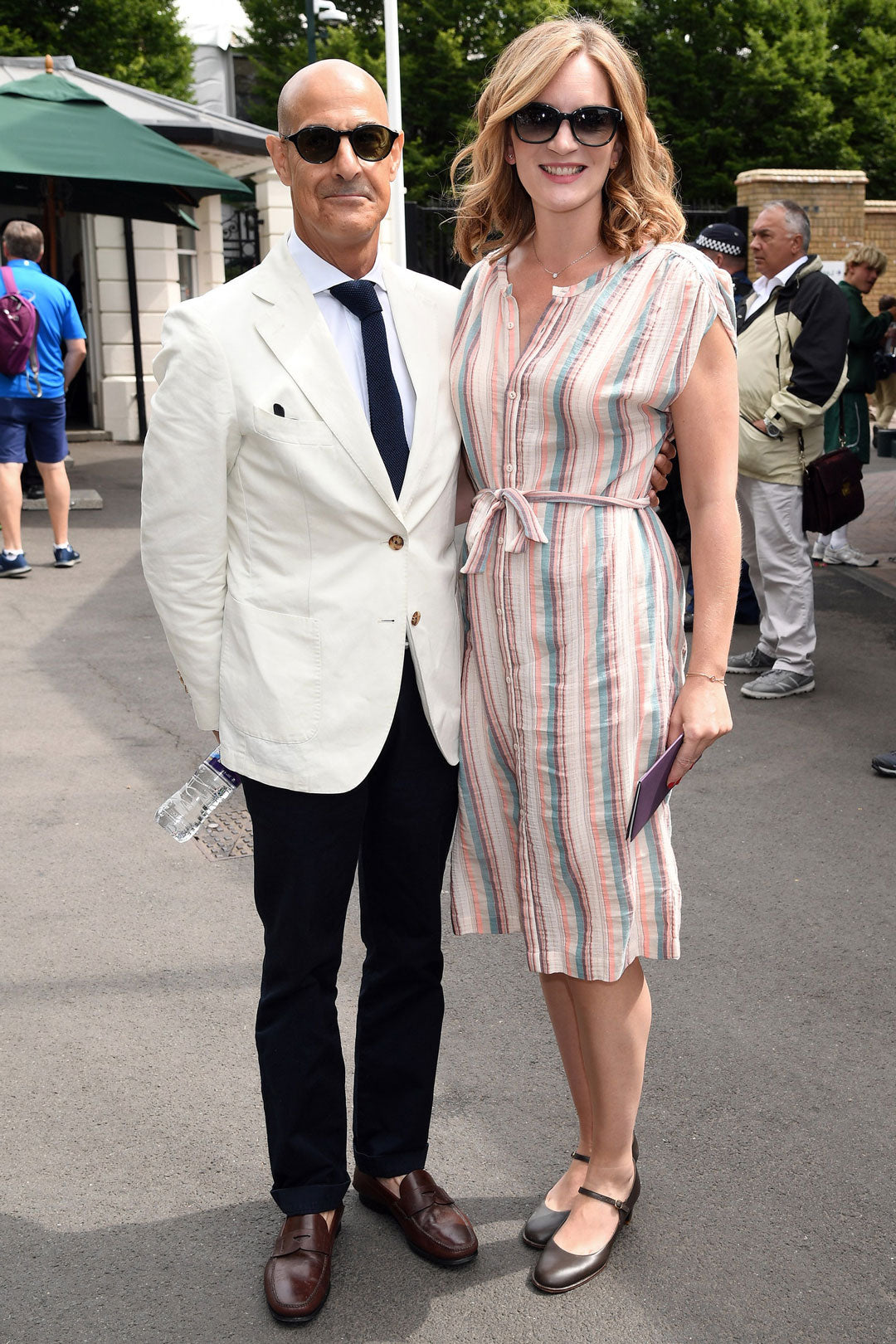 Stanley Tucci at Wimbledon wearing white suit sunglasses beside woman