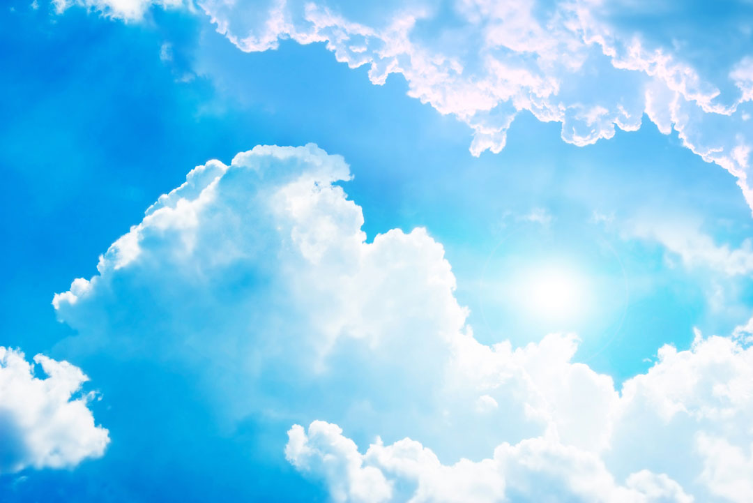 Strong sunlight bursting through white clouds and blue sky