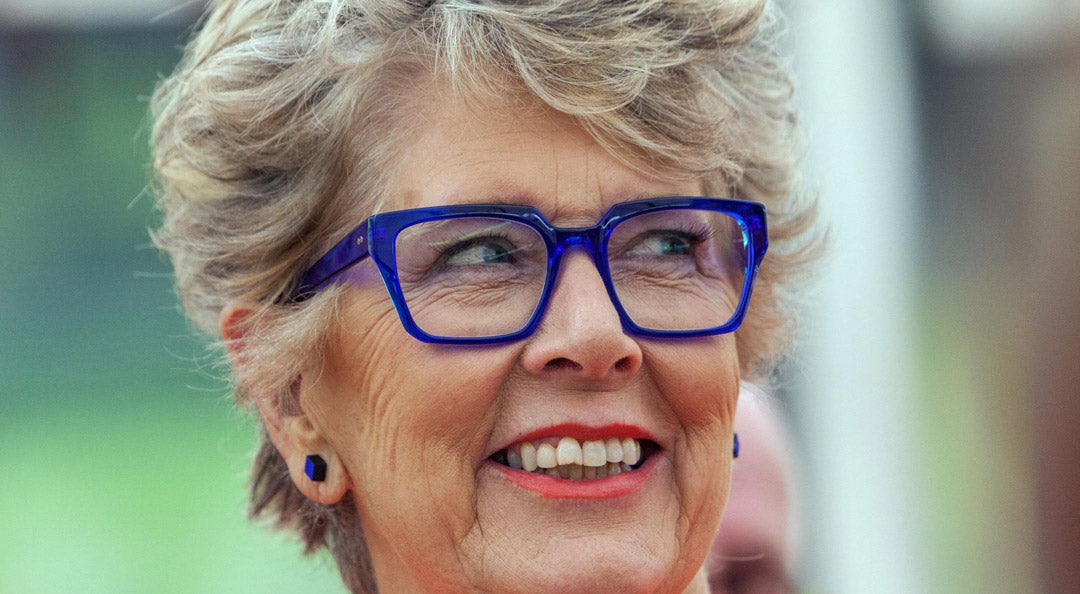 TV presenter Prue Leith wears a rectangular blue spectacle frame with blue earrings inside the Great British Bake Off tent