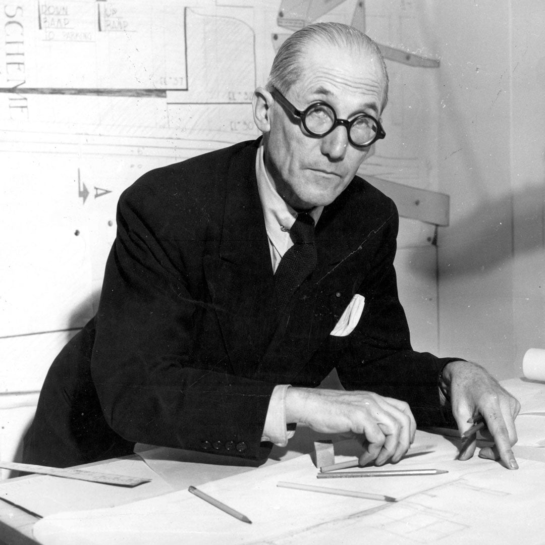 The famous architect Le Corbusier peering through his round spectacles at his drawing desk