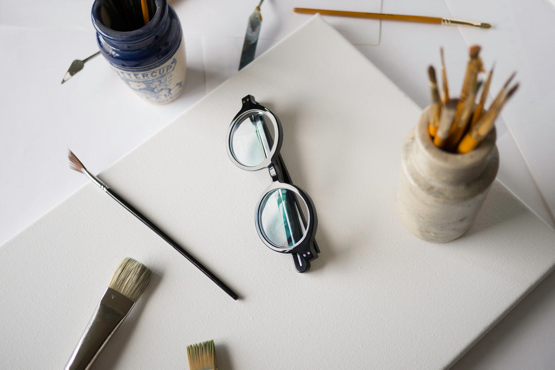 Thick black spectacles folded flat on white surface beside paint brushes