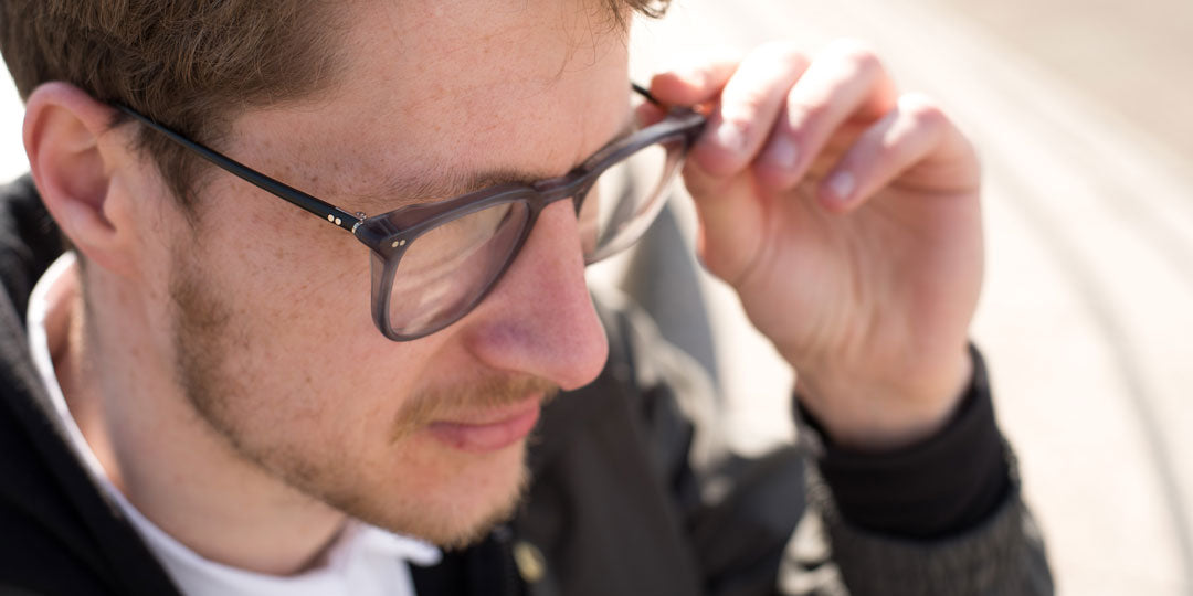 Three quarter view of young male wearing grey anti fatigue eyeglasses