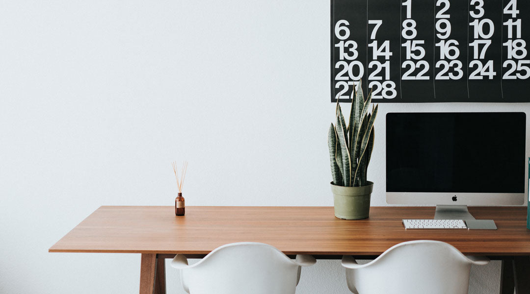 Tidy wooden office desk with computer calendar and two white seats