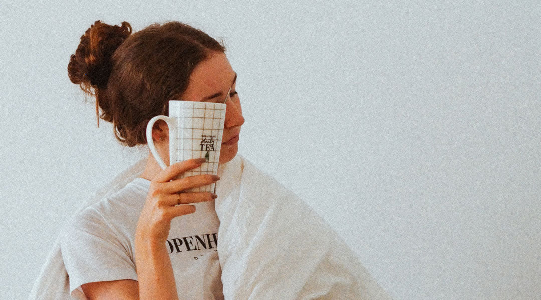 Tired female holding coffee mug to her face